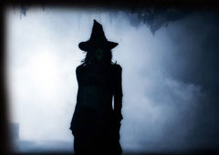 silhouette of a witch with a foggy, nightime background